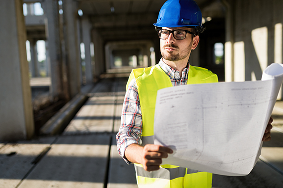 Engineers working on a building site holding a blue prints